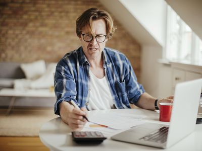 Man going through finances at table with papers, laptop, calculator, and cup and pot of coffee in front of him