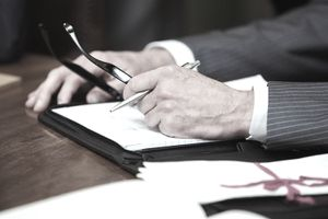 Closeup of a businessman's hands resting atop files and papers on a desk with a will in the foreground