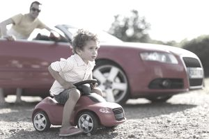 a young man sitting on a miniature car