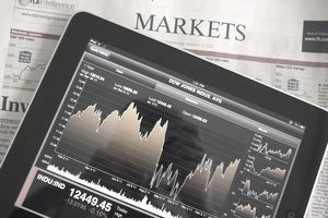 Tablet showing Dow Jones Avg. resting on Markets section of newspaper