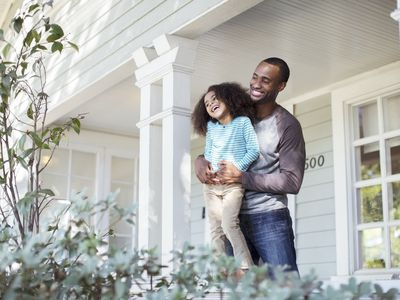 Happy father and daughter at home on their porch