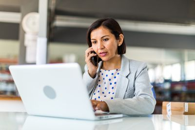woman with short hair in star-designed shirt talking on phone in front of laptop