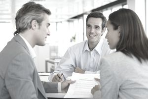 A couple discussing coverage with an independent insurance agent in an office setting.