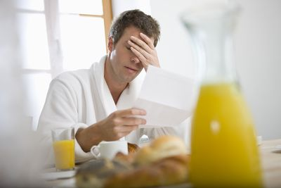 Man reading paper with bad news