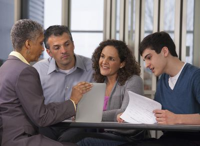 Parents and son talking with financial advisor about borrowing for college costs.