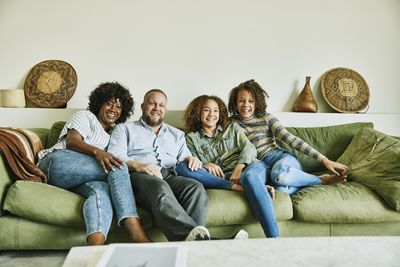 Portrait of smiling family sitting on couch in living room