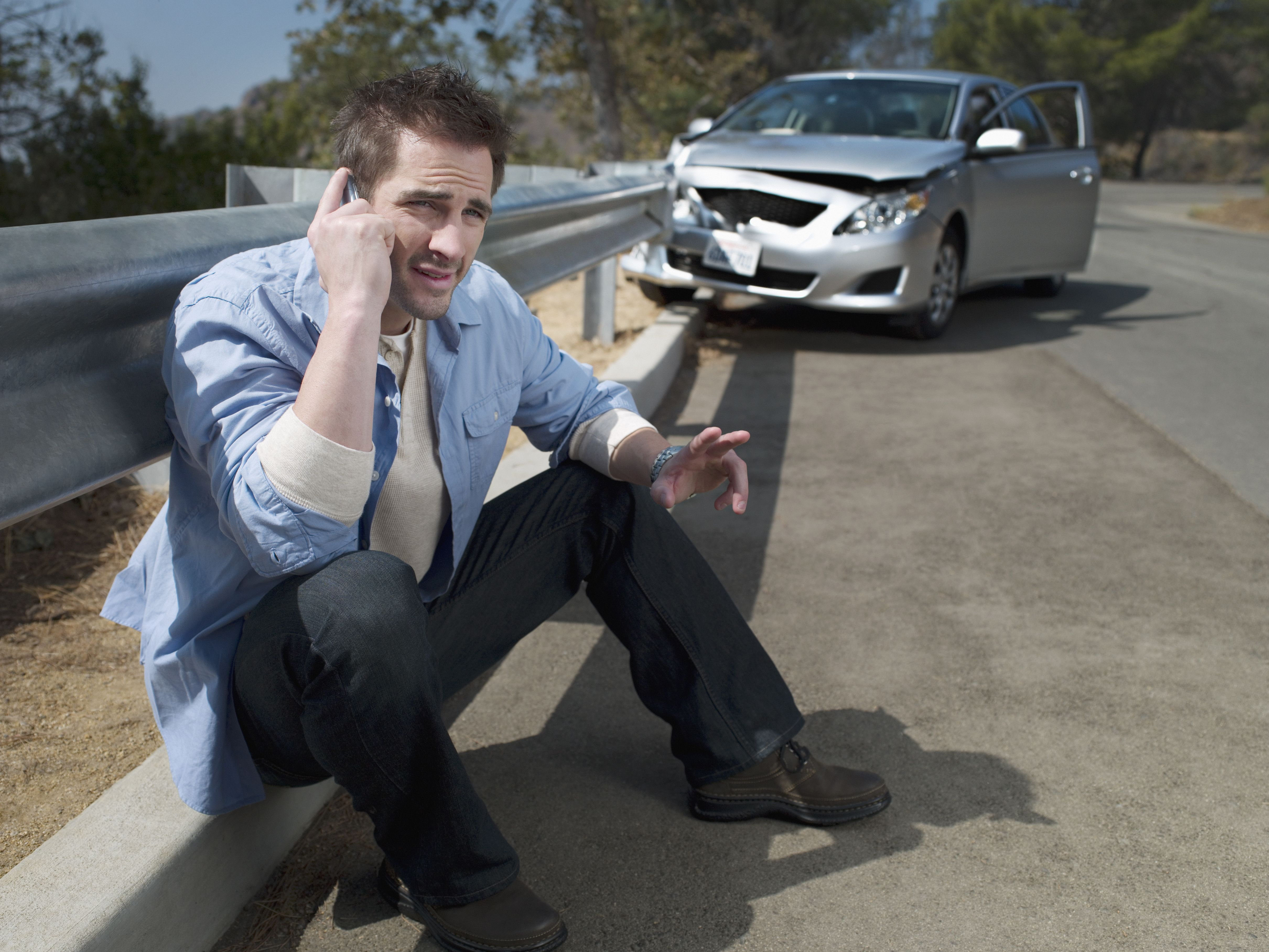 Man with crashed car calling for roadside assistance,
