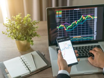 Investor analyzing stock market charts on laptop and smartphone.