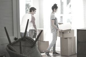 A young mixed race couple moving into a new home or apartment. They are inside, by a sunny window. The man is moving some furniture and the woman is putting the lid on a cardboard box. She is mixed race Hispanic and Pacific Islander ethnicity.