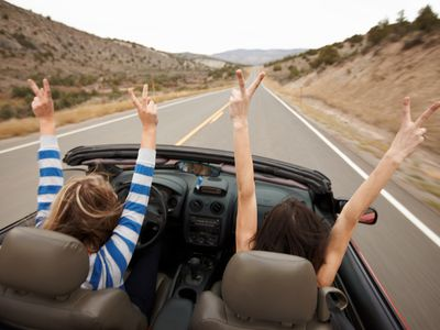 Driver and passenger with hands up in a convertible, driving down a highway