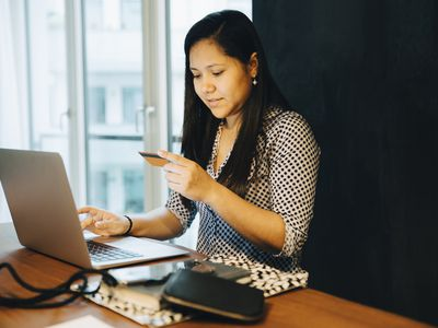 Woman sitting at a laptop and making an online purchase with a credit card.