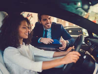 Woman behind the wheel of her new car in the dealership, with salesman going over the car's features