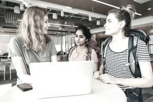 Three young women gather around a laptop