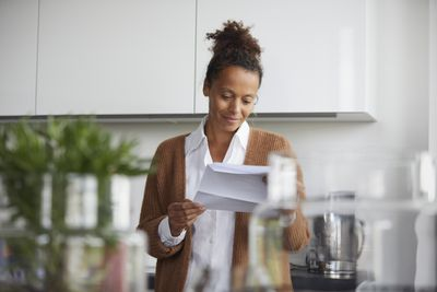 Person in brown sweater reviewing paperwork