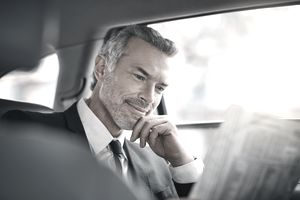 Cropped shot of a handsome mature businessman reading the paper while sitting in the backseat of a car during his morning commute