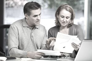 A middle-aged man and woman work on the bills together.