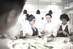 Chef mentoring students in restaurant kitchen