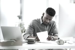 Businessman working at a desk with a notebook and computer