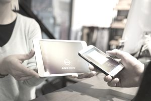 A store clerk holds a mobile payment terminal while a customer holds a smartphone