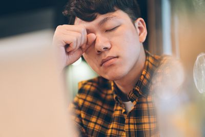 Exhausted young man rubbing eyes in front of a computer.