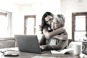 A young woman hugs her mother while both look at a laptop