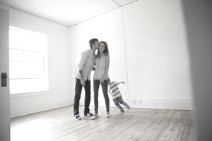 Young family kissing in empty new house