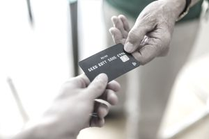 Close-up of two people exchanging a credit card
