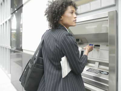 A woman uses an ATM machine to get cash from a bank.