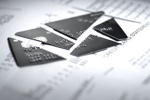 Close-up of cut pieces of credit card laying on top of a credit card statement