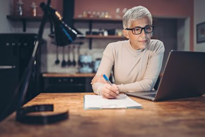 Bespectacled woman taking notes while working on laptop