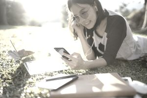 Asian female student smiling and lying down on the grass listening to music from mobile phone