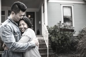 Portrait of young couple hugging and smiling in front of their new home