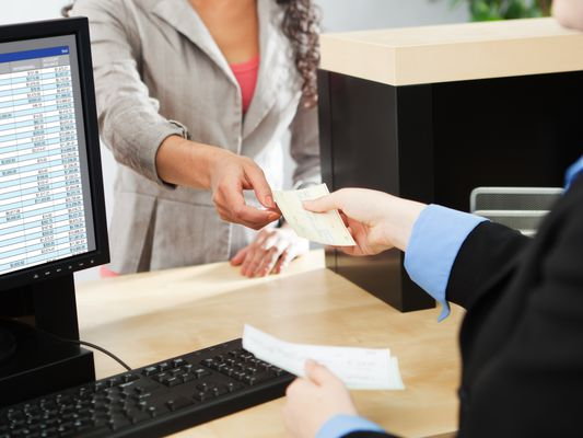 Bank Teller Service with Customer Deposit Transaction Over Business Counter