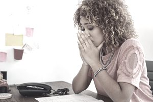 Unemployed woman stressed as she looks over her auto insurance bill