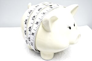A tape measure wrapped around a piggy bank indicating managing the money inside.