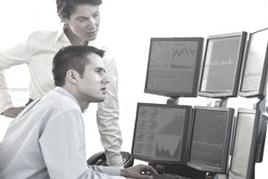Traders studying computer screens.