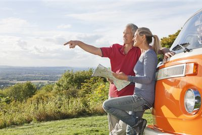 Older couple looking at map by a camper van and enjoying their retirement.