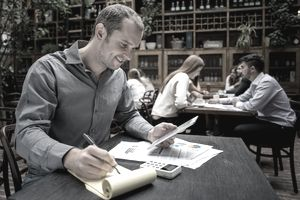 Bookkeeper working with paper and digital tablet at a restaurant