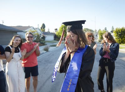A 22 year old caucasian young woman dressed in a graduation hat and gown is overcome by emotion while surrounded by her friends and family in front of her home during celebrating her graduation from college