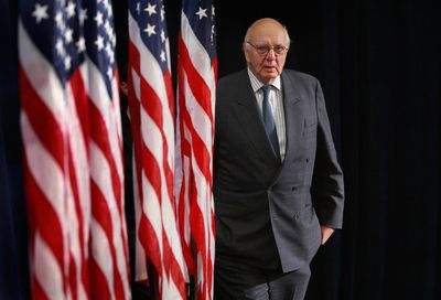 Paul Volcker next to American flags