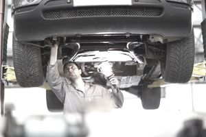 Car Mechanic Checks Under an Elevated Car, Holding a Light