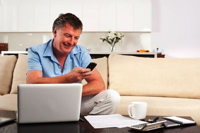 Mature man working on income tax at home with laptop and phone