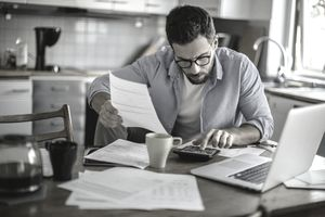 Man calculating expenses on a calculator while sitting at a table with a laptop and cup of coffee
