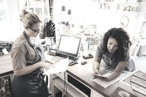 Two female colleagues discussing receipt with digital tablet in store