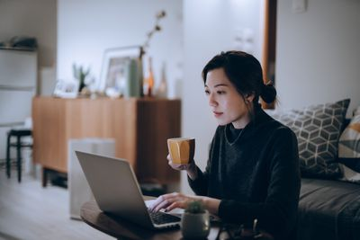 A woman drinks from a mug while working on a laptop at home