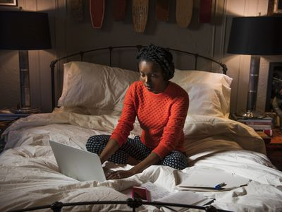 Young woman sitting on bed uses laptop in evening