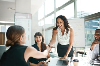 Woman shaking hands with colleagues