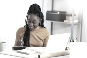 Close up of one African American woman using calculator, calculating finance at home, female hands and paper document at table close up, economist or financier writing report, student doing homework