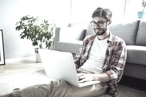 Young man sitting on living room floor working on laptop
