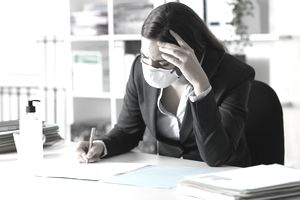 Worried executive wearing mask signing contract at office